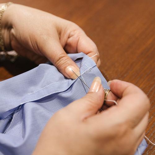 Sarta che cuce a mano con ago e filo dettaglio delle mani