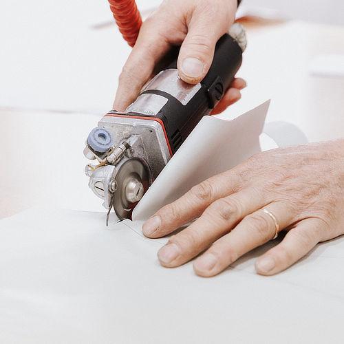 Sarto che taglia cartamodello e stoffa con attrezzatura professionale